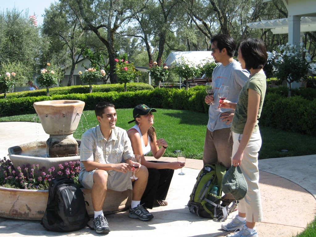 Group of people taste wine surrounding fountain